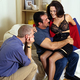 man and woman flirting whilst husband watches